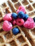 Βάφλα προγευμάτων που ολοκληρώνεται με τα φρέσκα respberries, μπλε μούρα και στοκ φωτογραφίες
