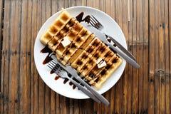 Βάφλες ζευγών με τη σάλτσα, τα βούτυρα, το κουτάλι και το δίκρανο σοκολάτας στο άσπρο πιάτο στον ξύλινο πίνακα Στοκ φωτογραφία με δικαίωμα ελεύθερης χρήσης