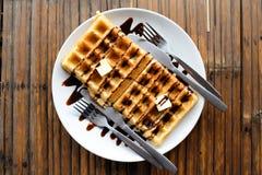 Βάφλες ζευγών με τη σάλτσα, τα βούτυρα, το κουτάλι και το δίκρανο σοκολάτας στο άσπρο πιάτο στον ξύλινο πίνακα Στοκ Φωτογραφία