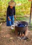 Βάφοντας τα δοχεία με τα ζωηρόχρωμα νήματα που βάφονται στο μπλε ύφασμα στοκ φωτογραφία με δικαίωμα ελεύθερης χρήσης