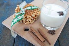Βάφλες με το γάλα, κανέλα, γλυκάνισο στο μπλε ξύλινο υπόβαθρο Στοκ Φωτογραφίες