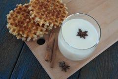 Βάφλες με το γάλα, κανέλα, γλυκάνισο στο μπλε ξύλινο υπόβαθρο Στοκ Φωτογραφία