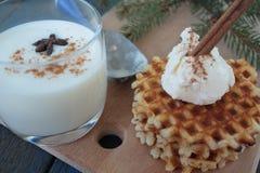 Βάφλες με το παγωτό και το γάλα, κανέλα, γλυκάνισο στο μπλε ξύλινο υπόβαθρο Στοκ φωτογραφία με δικαίωμα ελεύθερης χρήσης