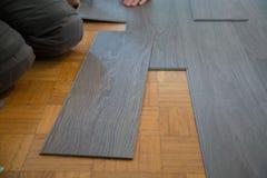 Βάλτε το βινυλίου πάτωμα στο πάτωμα παρκέ στοκ φωτογραφίες