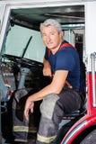 Βέβαια αρσενική συνεδρίαση πυροσβεστών στο φορτηγό Στοκ Εικόνες