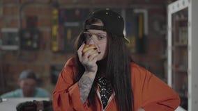 Βέβαια γυναίκα εργαζόμενος που τρώει το μήλο στο πρώτο πλάνο κοντά επάνω Το άτομο που εργάζεται με το ξύλο στο υπόβαθρο απόθεμα βίντεο