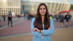 Βέβαια γυναίκα που στέκεται στο τετράγωνο πόλεων με τα διασχισμένα όπλα απόθεμα βίντεο