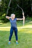 Βέβαια γυναίκα που στοχεύει με το τόξο και το βέλος στο δάσος Στοκ εικόνα με δικαίωμα ελεύθερης χρήσης
