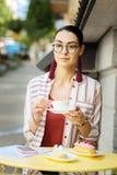 Βέβαια γυναίκα που τρώει τα επιδόρπια και που πίνει τον καφέ στοκ εικόνα