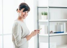 Βέβαια γυναίκα που χρησιμοποιεί ένα έξυπνο τηλέφωνο Στοκ φωτογραφία με δικαίωμα ελεύθερης χρήσης
