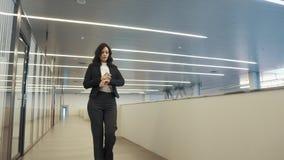 Βέβαια επιχειρησιακή γυναίκα που περπατά κάτω από την αίθουσα σε ένα κτίριο γραφείων νέα γυναίκα σε ένα μαύρο επιχειρησιακό κοστο φιλμ μικρού μήκους