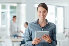 Βέβαια επιχειρησιακή γυναίκα που χρησιμοποιεί μια ταμπλέτα οθόνης αφής Στοκ φωτογραφίες με δικαίωμα ελεύθερης χρήσης