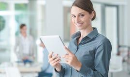 Βέβαια επιχειρησιακή γυναίκα που χρησιμοποιεί μια ταμπλέτα οθόνης αφής Στοκ Εικόνες
