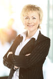 Βέβαια επιχειρησιακή γυναίκα στο γραφείο με μια ομάδα πίσω από την Στοκ Εικόνες