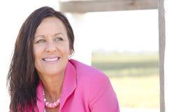 Βέβαια ευτυχής ώριμη γυναίκα στο ροζ Στοκ εικόνα με δικαίωμα ελεύθερης χρήσης