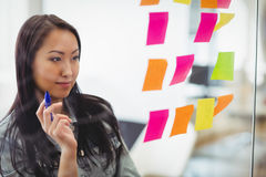 Βέβαια δημιουργική επιχειρηματίας που εξετάζει τις πολυ χρωματισμένες κολλώδεις σημειώσεις Στοκ Εικόνες