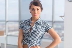 Βέβαια θετική νέα τοποθέτηση γυναικών, χαμόγελο Πανέμορφο φιλικό να φανεί κορίτσι brunette, που στέκεται λοξά στοκ εικόνες με δικαίωμα ελεύθερης χρήσης