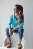 Βέβαια μοντέρνη αστική νέα γυναίκα που κοιτάζει μακριά καθμένος στην καρέκλα, στο γκρίζο υπόβαθρο Στοκ Εικόνα
