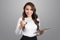 Βέβαια νέα ασιατική γυναίκα που κρατά το ψηφιακό tabler που παρουσιάζει credi στοκ φωτογραφία