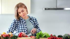 Βέβαια νέα γυναίκα που τεμαχίζει το φρέσκο κόκκινο γλυκό πιπέρι στον ξύλινο πίνακα που χρησιμοποιεί τη μέση κινηματογράφηση σε πρ απόθεμα βίντεο