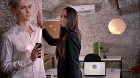 Βέβαια νέα γυναίκα που ωθεί άλλη γυναίκα στον τοίχο, γυναίκα που πηγαίνει μακριά στο σύγχρονο γραφείο, λεσβιακή έννοια απόθεμα βίντεο