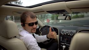 Βέβαια συνεδρίαση επιχειρηματιών στο αυτοκίνητο, που δίνει αντίχειρας-επάνω στη χειρονομία, επιχειρησιακός οδηγός Στοκ Εικόνες