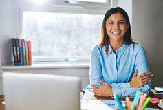 Βέβαια χαμογελώντας γυναίκα στο γραφείο πίσω από το lap-top Στοκ φωτογραφία με δικαίωμα ελεύθερης χρήσης
