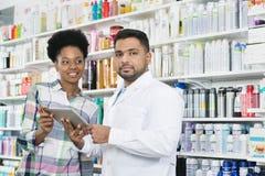 Βέβαια ψηφιακή ταμπλέτα εκμετάλλευσης φαρμακοποιών από τον πελάτη στοκ εικόνες