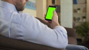 Βέβαιες αρσενικές πολιτικές ειδήσεις ανάγνωσης στο smartphone με την πράσινη οθόνη, app απόθεμα βίντεο