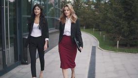 Βέβαιες επιχειρησιακές γυναίκες που περπατούν κάτω από την οδό κίνηση αργή φιλμ μικρού μήκους
