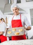 Βέβαιες πίτσες εκμετάλλευσης αρχιμαγείρων στο δίσκο στην κουζίνα στοκ φωτογραφίες