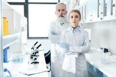 Βέβαιοι επιστήμονες στα άσπρα παλτά που εξετάζουν τη κάμερα και την τοποθέτηση Στοκ Φωτογραφία
