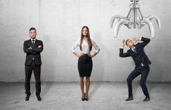 Βέβαιοι επιχειρηματίες που στέκονται κατ' ευθείαν και φοβησμένο προστατευτικό κάλυμμα επιχειρηματιών ο ίδιος από το γιγαντιαίο μη Στοκ εικόνες με δικαίωμα ελεύθερης χρήσης
