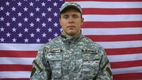 Βέβαιος αμερικανικός στρατιώτης που διπλώνει τα όπλα στο υπόβαθρο σημαιών, επαγγελματισμός φιλμ μικρού μήκους