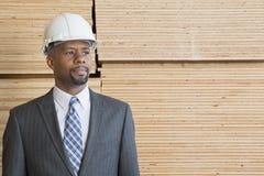 Βέβαιος αρσενικός ανάδοχος αφροαμερικάνων που κοιτάζει μακριά στεμένος μπροστά από τις συσσωρευμένες ξύλινες σανίδες Στοκ Εικόνα