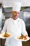 Βέβαιος αρσενικός αρχιμάγειρας με τα μαγειρευμένα τρόφιμα στην κουζίνα στοκ φωτογραφία με δικαίωμα ελεύθερης χρήσης