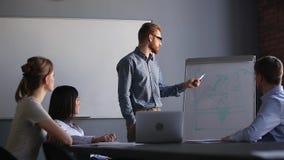 Βέβαιος αρσενικός εκπαιδευτής επιχειρησιακών ομιλητών που κάνει την εταιρική παρουσίαση διαγραμμάτων κτυπήματος φιλμ μικρού μήκους