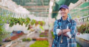 Βέβαιος αρσενικός κηπουρός γεωργίας που εξετάζει τις σε δοχείο εγκαταστάσεις λουλουδιών φιλμ μικρού μήκους