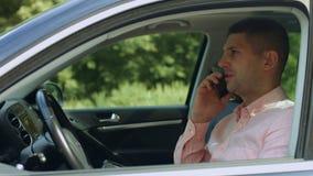 Βέβαιος αρσενικός οδηγός που μιλά στο κινητό τηλέφωνο στο αυτοκίνητο απόθεμα βίντεο