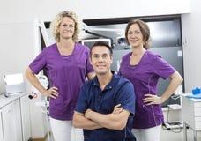 Βέβαιος αρσενικός οδοντίατρος με τις γυναίκες βοηθοί στοκ εικόνα