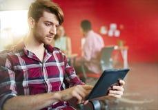 Βέβαιος αρσενικός σχεδιαστής που εργάζεται σε μια ψηφιακή ταμπλέτα στον κόκκινο δημιουργικό χώρο γραφείου Στοκ Εικόνες