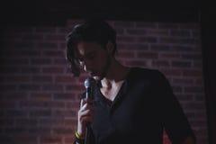 Βέβαιος αρσενικός τραγουδιστής που αποδίδει στη συναυλία μουσικής στοκ εικόνα