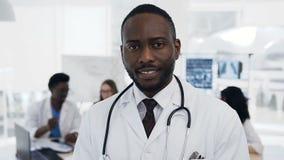 Βέβαιος αφρικανικός αρσενικός γιατρός με την ομάδα του cowoker στο υπόβαθρο στο νοσοκομείο φιλμ μικρού μήκους