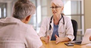 Βέβαιος γιατρός που συζητά τις ανησυχίες υγείας με το ηλικιωμένο άτομο στοκ φωτογραφίες με δικαίωμα ελεύθερης χρήσης