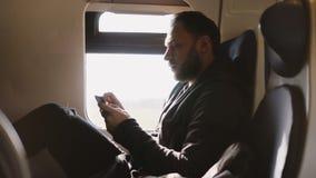 Βέβαιος επιτυχής καυκάσιος επιχειρηματίας που χρησιμοποιεί το κινητό γραφείο app smartphone διακινούμενος στην έδρα παραθύρων τρα φιλμ μικρού μήκους
