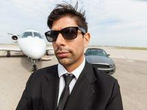 Βέβαιος επιχειρηματίας μπροστά από το αυτοκίνητο και ιδιωτικός Στοκ εικόνες με δικαίωμα ελεύθερης χρήσης