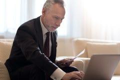Βέβαιος επιχειρηματίας που εξετάζει τη γραφική εργασία στο lap-top Στοκ Εικόνα