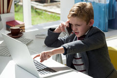 Βέβαιος επιχειρηματίας που μιλά μέσω του κινητού τηλεφώνου δείχνοντας στο lap-top Στοκ φωτογραφίες με δικαίωμα ελεύθερης χρήσης