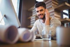 Βέβαιος επιχειρηματίας που μιλά στο κινητό τηλέφωνο στο γραφείο υπολογιστών Στοκ φωτογραφία με δικαίωμα ελεύθερης χρήσης