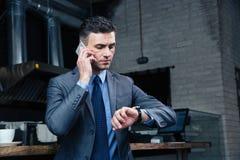 Βέβαιος επιχειρηματίας που μιλά στο τηλέφωνο στον καφέ Στοκ εικόνες με δικαίωμα ελεύθερης χρήσης